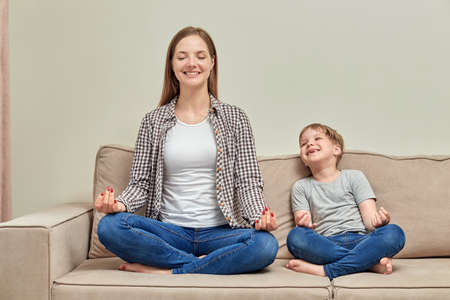 A young mother teaches her child how to meditate correctly. Yoga class at home with a child. Happy healthy family. Standard-Bild