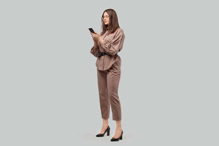 Full length young beautiful business woman in a beautiful business suit and high heels. Gray background.