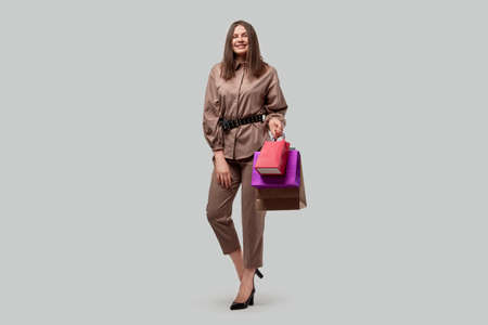 Full growth business woman holding shopping bags in her hands. Shopping for holiday gifts. Gray background.