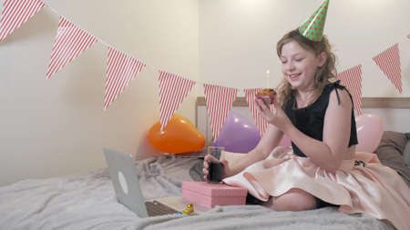 The girl will blow out the candles on the birthday cake. Beautiful decorated room with flags and balloons. Communication using social networks and video communication.