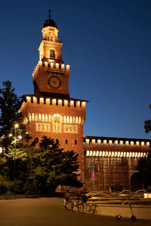 Sforza Castle with a fountain at night. Beautiful illumination of the building in warm colors. Milan Italy 08.2020