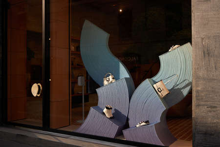 Modern showcase of a fashion store. Shoe and bag shop. A statue made up of many winding lines. Milan Italy 08.2020