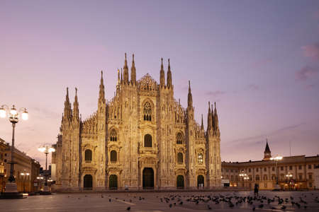 Facade of the beautiful historic Duomo building at night. Against the background of the sunset.