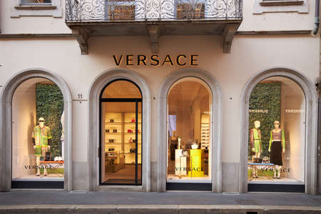Illuminated showcase of Versace store. Front door to the store. Mannequins in fashionable clothes are on display. Milan Italy 08.2020