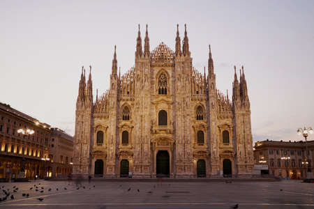 Facade of the beautiful historic Duomo building at night. The building is illuminated by lanterns. Milan Italy 08.2020