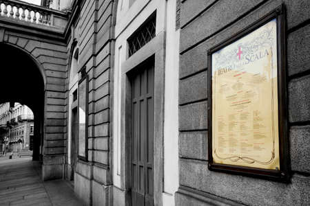 Black and white photo of the entrance to the Teatro alla Scala. The poster, the poster is colored, soft bed color. Old paper. Milan, Italy. 22.08.2020