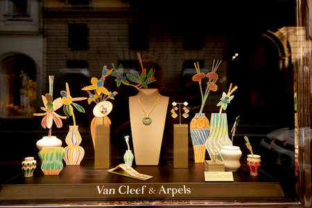 Showcase with expensive Van Cleef and Arpels jewelry. Illuminated showcase with lighting. Milan Italy 08.2020