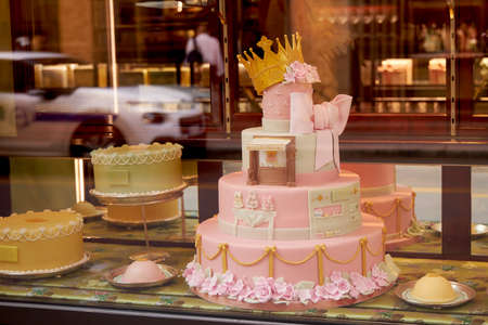 On the window is a beautiful festive pink cake for girls, a cake with a crown. Big pink bow. 写真素材
