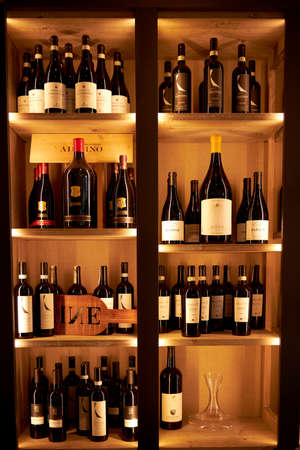 Large beautiful wooden shelf with wine in the restaurant. Vertical phono. Large selection of varied wines. Milan Italy. 08.2020