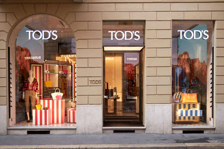 Beautiful bright showcase of TODS store. The front door to the store is next to two windows. Milan Italy 08.2020