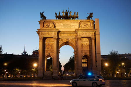 Milano city center arco della pace at sunset monument. A police car is passing by. Milan Italy 08.2020 報道画像