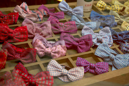 Showcase in a store with beautiful multi-colored bow ties. Glare of glass. Each gastuk is in a separate cell.