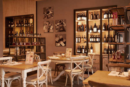 Beautiful trendy cafe with delicate beige light. Cozy place, white tables. The cafe is decorated with shelves with wine. Milan Italy. 08.2020