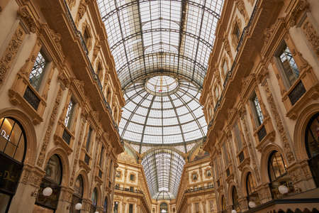 Shot of the famous Galleria Vittorio Emanuele II, the famous luxury shopping mall, showing the spectacular view of an almost golden gate to luxury. Milan Italy. 22.08.2020