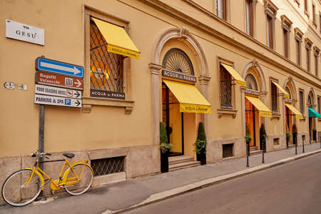 There is a bright yellow bicycle near the beautiful building. Fashionable street in Milan. Milan Italy 08.2020
