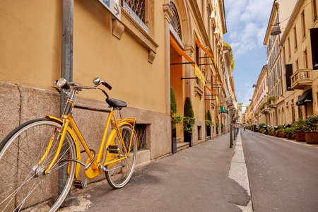 A beautiful bright yellow bicycle stands on a beautiful old street. Cycling around the cities of Europe. Historic old buildings. Narrow street. Milan Italy 08.2020 写真素材