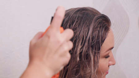 A hand applies a protective spray to light, wet hair. Beauty saloon. Professional hair care.