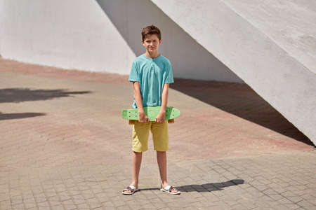 Young handsome brunette guy walking in the park with penny skate. Summer walks. 写真素材