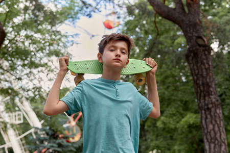 Portrait of a young handsome guy walking in the park with a skateboard. Summer walks.