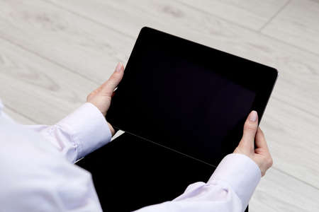 In womens hands, an electronic tablet in a horizontal position with a black screen. Light boards on the background. Womens hands in a white official shirt.
