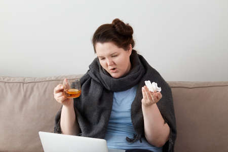 A sick woman sitting at home with hot tea and a paper towel, working online, with a laptop.