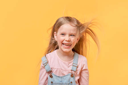 Developing beautiful blonde hair for a little girl. Yellow isolated background.