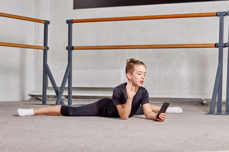 A young man is lying on the floor on the splits in the gym and holding a smartphone. Sports lifestyle and body flexibility.