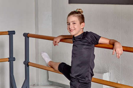Portrait of a sporty young guy. Training in ballet and gymnastics. Training class.