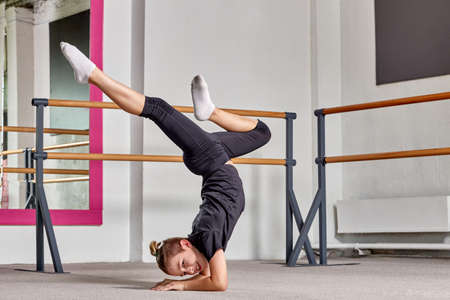 A young man stands on his head, legs apart in a ballet school on the carpet. Sports lifestyle and body flexibility.