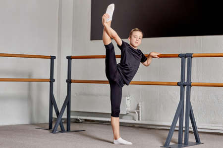 A young man does stretching exercises at a sports school. The leg is raised high up. Sports lifestyle and body flexibility.