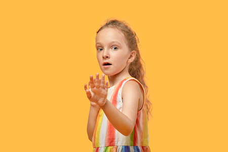 The girl with long blond hair was startled and put her hands out in front of her. Dress with multicolored stripes. Orange isolated background.
