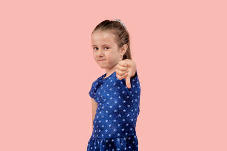 A frustrated girl glares at the camera and makes a thumbs-down gesture in a blue dress. Pink isolated background.