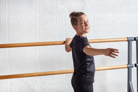 A beautiful young man looks into the camera and learns ballet at a ballet school. The hand on the ballet Barre.