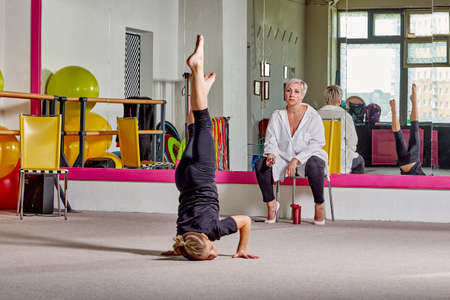 A young man stands on his head under the supervision of a teacher. Sports lifestyle and body flexibility. A woman speaks to a student.