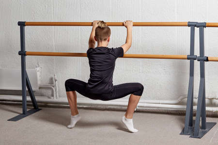 A sporty young man stands with his back to the bar and trains to learn ballet. Ballet school.
