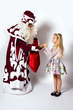 Little girl in a beautiful dress receives a gift from santa claus, Ded Moroz.