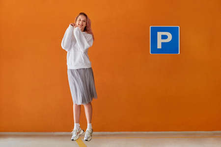 Beautiful cheerful girl bounces on the spot near the Parking sign. White jacket, grey skirt. The orange wall.