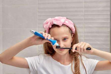 Blonde girl uses a toothbrush and toothpaste in the bathroom. Morning routine.
