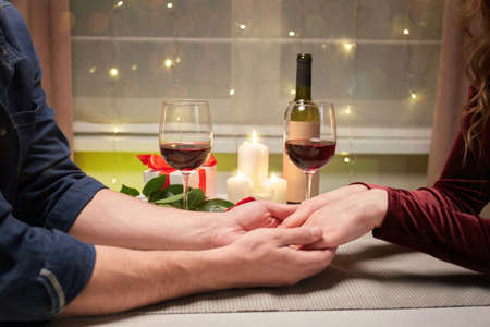 Hands of a young couple holding hands on a romantic evening. A holiday for lovers. Valentines day.