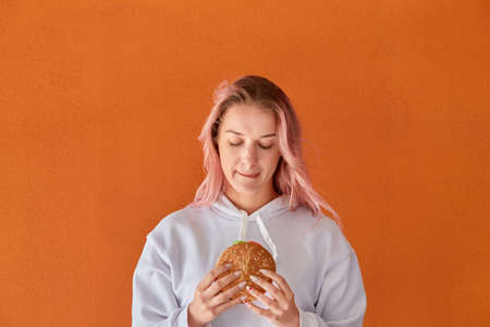 A young woman is holding a large delicious Burger. The concept of harmful nutrition. Orange background.