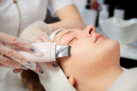 Close-up of the face of a woman who is doing an electronic peeling in gloves. Beauty salon.