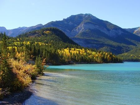 Colorful fall foliage surrounding a blue lake in the mountains photo