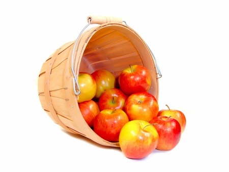 basket: A group of apples spilling from a wooden farmers basket