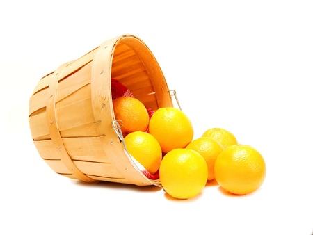 Oranges déversant du panier du fermier en bois, sur fond blanc Banque d'images