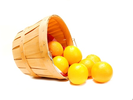 Oranges spilling out of a wooden farmer's basket, on white Stockfoto