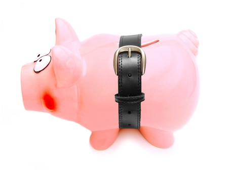 failing: Piggy bank with a belt wrapped around its shrinking body Stock Photo