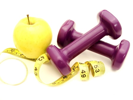 cutback: Healthy lifestyles - apple and weights with measuring tape  Stock Photo