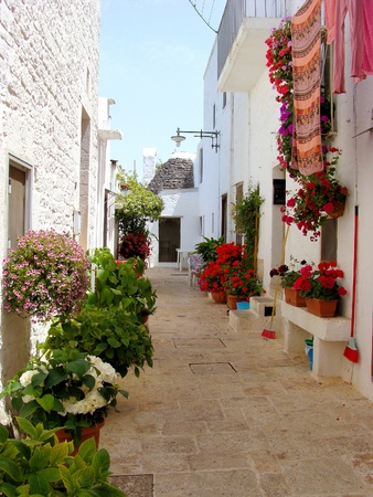 south italy: Flower lined street in Alberobello, Italy  Stock Photo