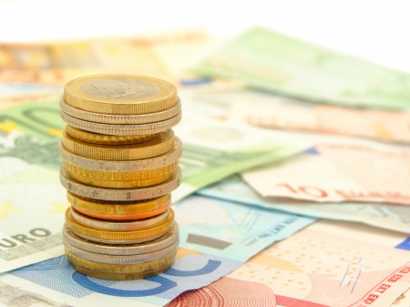 euro notes: Single stack of coins with bank notes in the background  Stock Photo