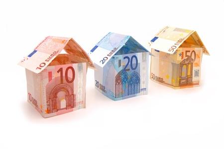billets euro: Trois maisons faites de l'argent sur un fond blanc